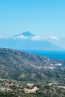 Aegean sea coast with hills full of greenery, buildings near the coast with high mountain reaching the clouds greece