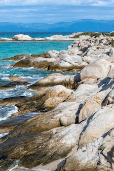 Aegean sea coast with rocks, bushes and land, blue water with waves, greece