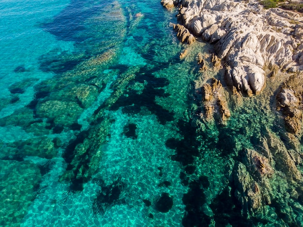 Aegean sea coast with rocks near the shore and under the blue transparent water, view from the drone, greece