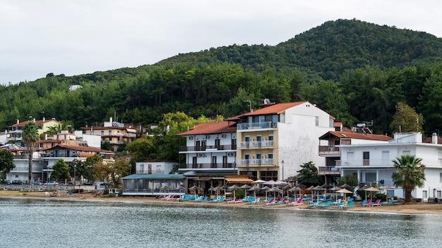 Costa del mar egeo, ombrelloni e lettini in spiaggia, edifici in fila