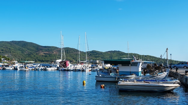 Aegean sea port with multiple moored yachts and boats, clear weather in neos marmaras, greece