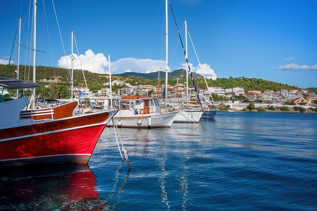 Aegean sea port with multiple moored yachts and boats, town located on a hill with greenery, clear weather in neos marmaras, greece