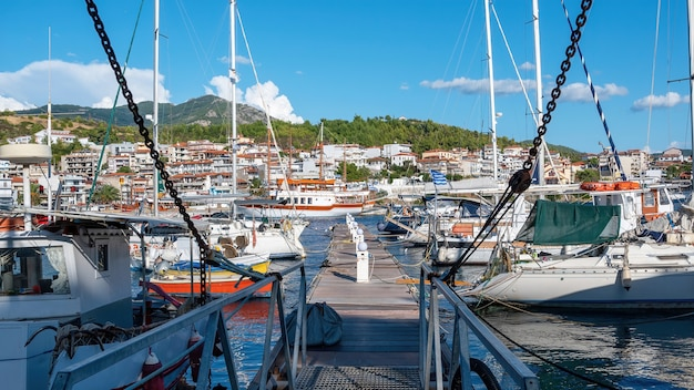 Aegean sea port with multiple moored yachts and boats, wooden pier, town located on a hill with greenery, clear weather in neos marmaras, greece