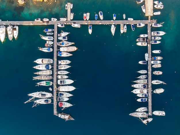 Aegean sea port with multiple moored yachts near piers, blue water, view from the drone, greece