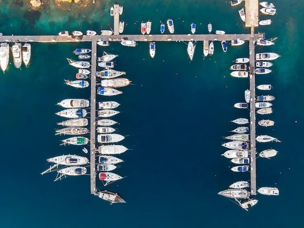 부두, 푸른 물, 무인 항공기, 그리스에서보기 근처에 여러 정박 된 요트가있는에게 해 항구