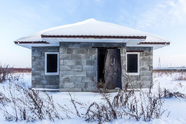 Дом из газобетона со сломанной дверью после ограбления