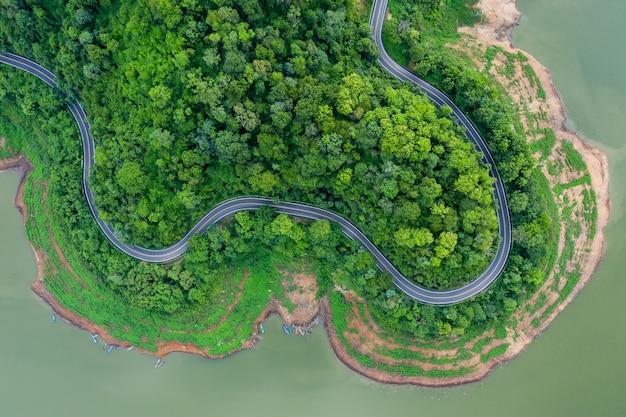 Вид сверху на зеленые горные леса и реку в сезон дождей и изогнутую дорогу на холме, соединяющем сельскую местность