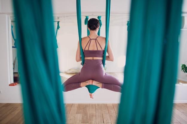 공중 반중력 요가 개념입니다. 녹색 해먹을 사용하여 반중력 요가 스튜디오에서 플라이 요가를 연습하는 여성.