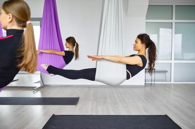 Воздушная антигравитационная йога, женские групповые тренировки, подвешивание на гамаках. фитнес, пилатес и танцевальные упражнения смешивают. женщины на тренировке йоги в спортивной студии