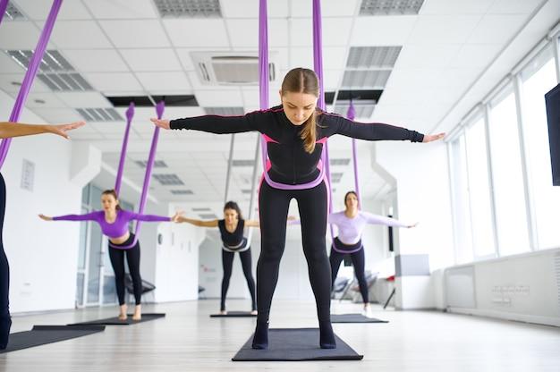 Воздушная антигравитационная йога, женские групповые тренировки с гамаками. фитнес, пилатес и танцевальные упражнения смешивают. женщины на тренировке йоги в спортивной студии