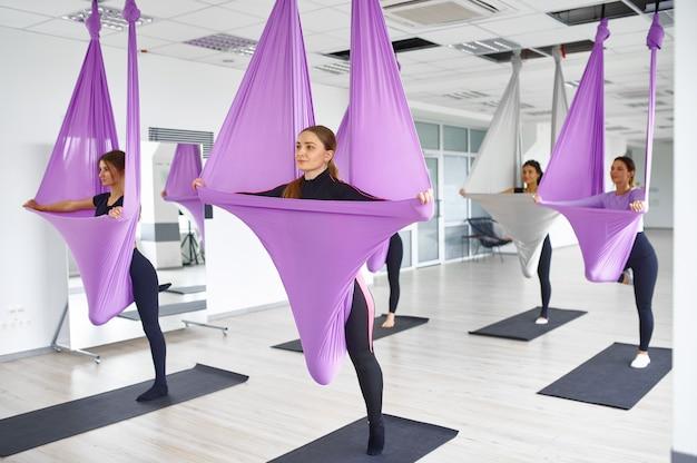Воздушная антигравитационная йога, групповые занятия с гамаками. фитнес, пилатес и танцевальные упражнения смешивают. женщины на тренировке йоги в спортивной студии