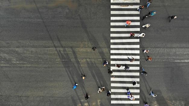 Aerial. asphalt road with zebra pedestrian crosswalk and crowd of people. top view.