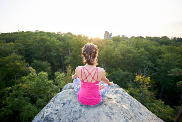 Aerial back view of young slim tourist woman sitting on big mountain rock, doing yoga at sunrise on green trees tops forest background