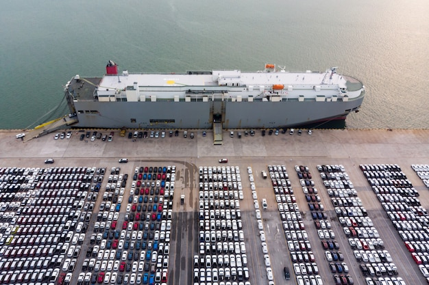 Aerial bird's-eye view, new cars produced several times a year at industrial estate for import export around in the world