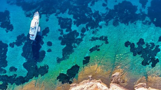 청록색 맑은 물이 있는 열대 바다와 바위 해변의 공중 조감도 사진 무인 항공기