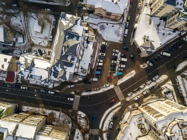 高層ビル、駐車場、道路標識のある通りに沿って移動する車のある近代的な都市の空中の黒と白の冬のトップビュー。都市の景観、上からの眺め。