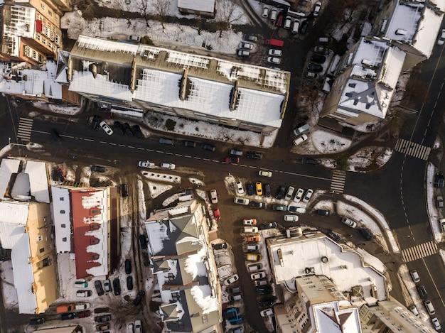 高層ビル、駐車場、道路標識のある通りに沿って移動する車のある近代的な都市の空中の黒と白の冬トップビュー。都市の景観、上からの眺め。