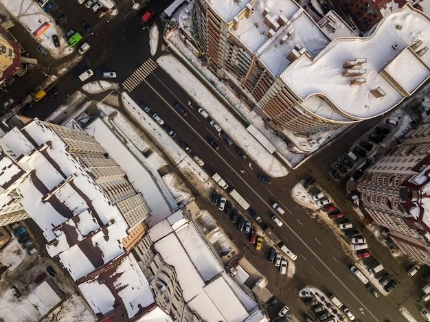 道路標示が付いている通りに沿って高層ビル、駐車中、移動中の車がある近代的な都市の空中の黒と白の冬のトップビュー。都市の景観、上からの眺め。