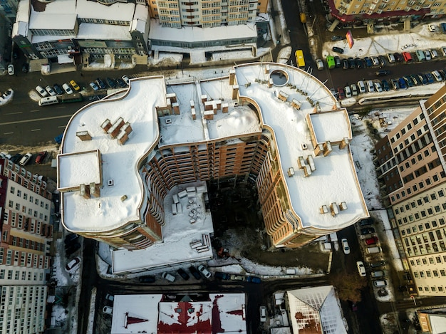 Aerial black and white winter panoramic top view of modern city with tall apartment complex buildings snowy roof, parked and moving cars along streets. urban infrastructure, view from above.