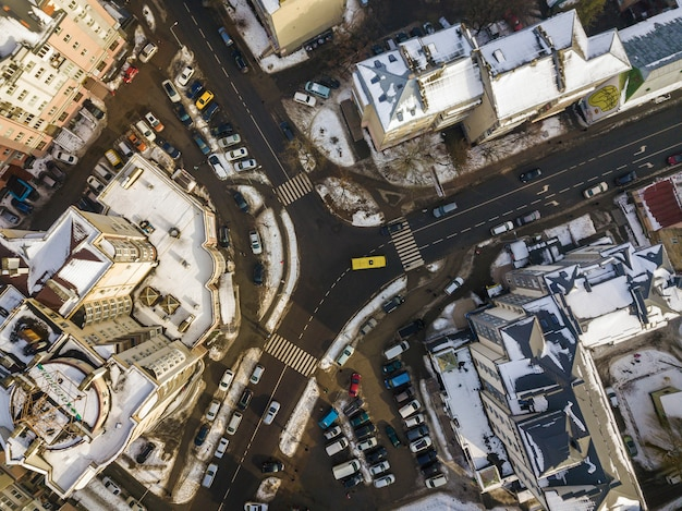 Aerial black and white winter top view of modern city with tall buildings, parked and moving cars along streets with road marking.