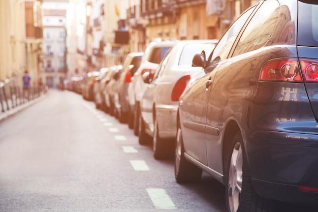 屋外の空中駐車場、列に並んだ後部車通りの道路事務所市街地の脇に駐車。フィルタートーンレトロヴィンテージウォームエフェクト付き。交通線。輸送の概念。