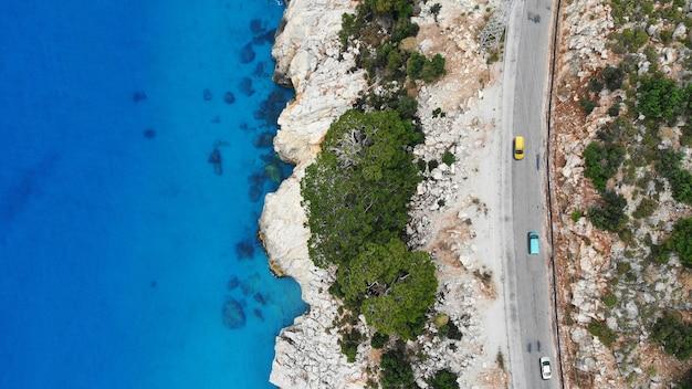 Антенна. автомобили едут по трассе у средиземного моря. вид сверху с дрона.