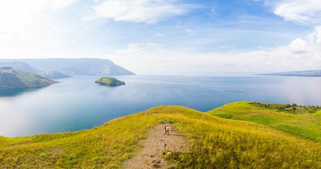 Антенна: пара, походы на вулкан сверху смотровой площадки над озером тоба и остров самосир суматра индонезия. летние развлечения мужчина и женщина с удовольствием