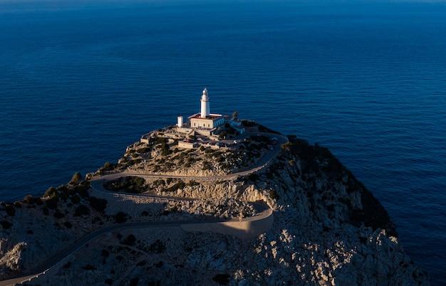 海の真ん中に上に建てられた白い塔のある高い岩の崖の空中遠景