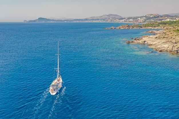空中ドローン、ロードス島ファリラキ湾をクルージングする帆船の鳥瞰図