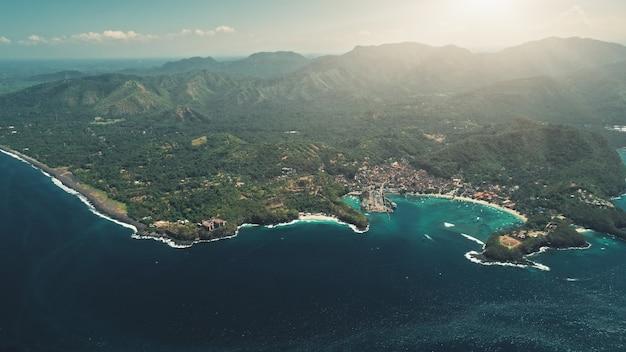 熱帯の島のクリスタルオーシャンハーバーベイと緑の森の山々の上の空中ドローン飛行