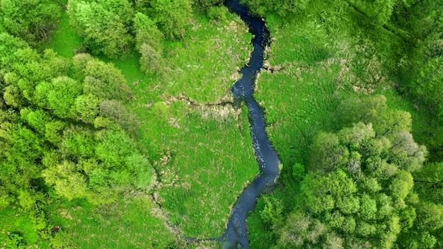 Антенна. дрон летает над рекой, зеленым лугом и лесом