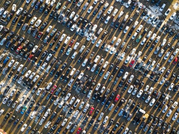駐車場、平面図に駐車されている多くの車の空中ドローン画像。