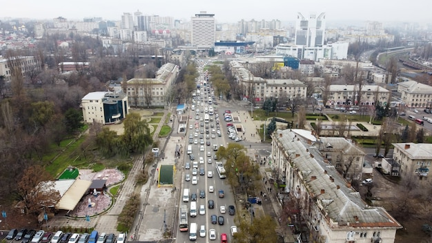 Aerial drone panorama view of chisinau, street with multiple residential and commercial buildings, road with multiple moving cars, park with bare trees