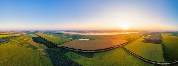 Aerial drone panorama view of nature in moldova at sunset. smoke from a fire, wide fields, road, sun