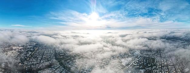 キシナウの空中ドローンパノラマビュー。複数の建物、道路、雪、裸の木。 無料写真