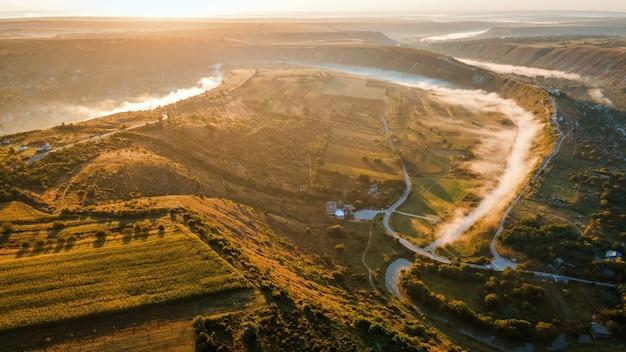 Панорама с высоты птичьего полета на старый орхей в долине заката с рекой и туманной деревней