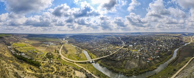 Aerial drone panorama view of a village located near a river and hills, fields, godrays, clouds in moldova