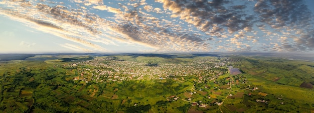 Aerial drone panoramic view of a village, green fields and hills in the distance, moldova