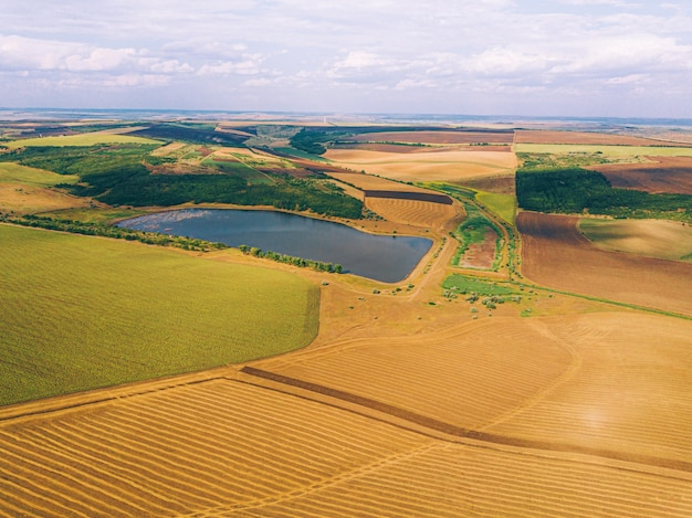 Aerial drone photo of amazing landscape with crops and lake, agriculture concept.