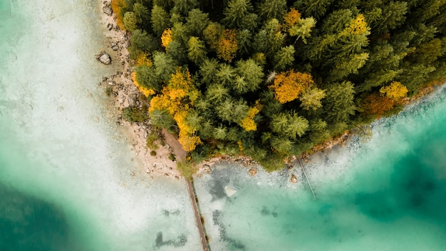 Aerial drone photo of lake, bridge, forest, and turquoise water in bavarian mountains