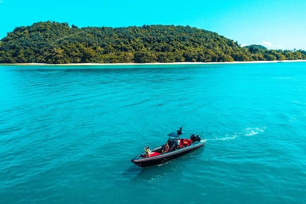熱帯のエメラルドの澄んだ水海を高速でクルージングするインフレータブルパワーボートの空中ドローン写真