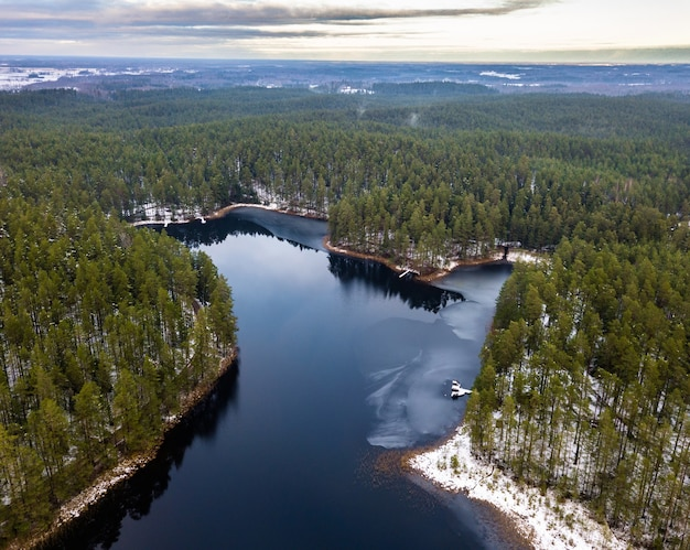 Aerial drone photo of partly frozen lake in a snowy winter, surrounded with green forests