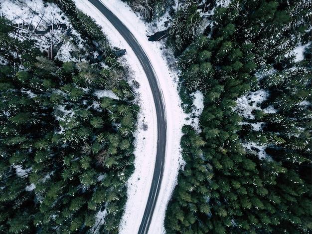 눈이 내리는 숲 사이 겨울 도로의 공중 무인 항공기 사진