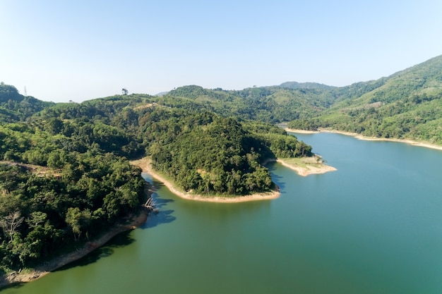 Aerial drone shot bird eye view mountain lake with rainforest lake surrounded by mountains and reflection in the water.