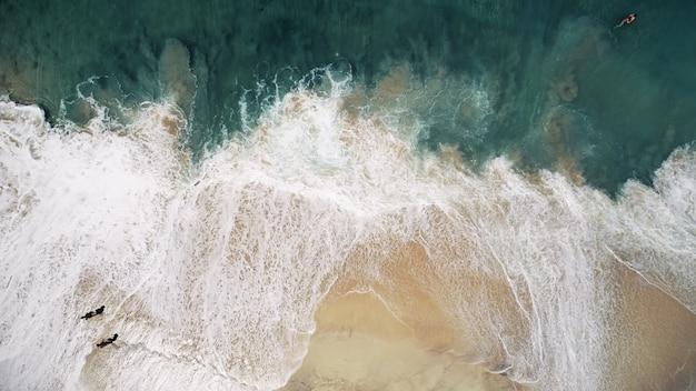 공중 무인 항공기는 거대한 바다 해변 파도 노란색 모래와 수정 같은 파란색과 녹색 물 풍경을 촬영