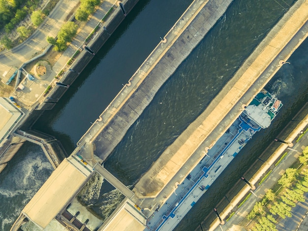 Aerial drone shot of river gateway structure for barge cargo ships f