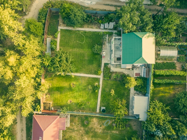Aerial drone shot of summer countryside cottage with garden f