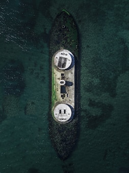 Aerial drone shot of a wrecked ship in the sea