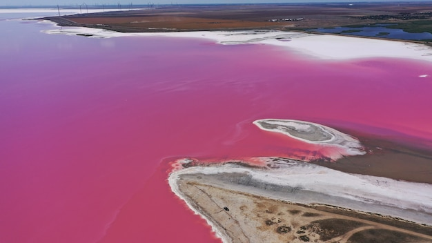 Фото сверху вниз с воздушного дрона естественного розового озера и побережья геническа, украина. озеро естественно розовеет из-за солей и мелких рачков артемии в воде. это чудо встречается редко.