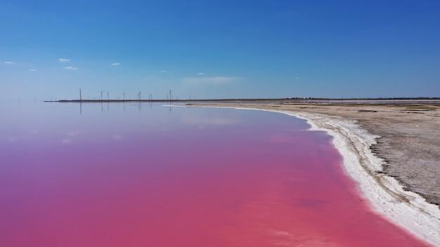 Фото сверху вниз с воздушного беспилотника естественного розового озера, голубого неба и побережья куяльника в одессе, украина. озеро естественно розовеет из-за солей и мелких рачков артемии в воде.